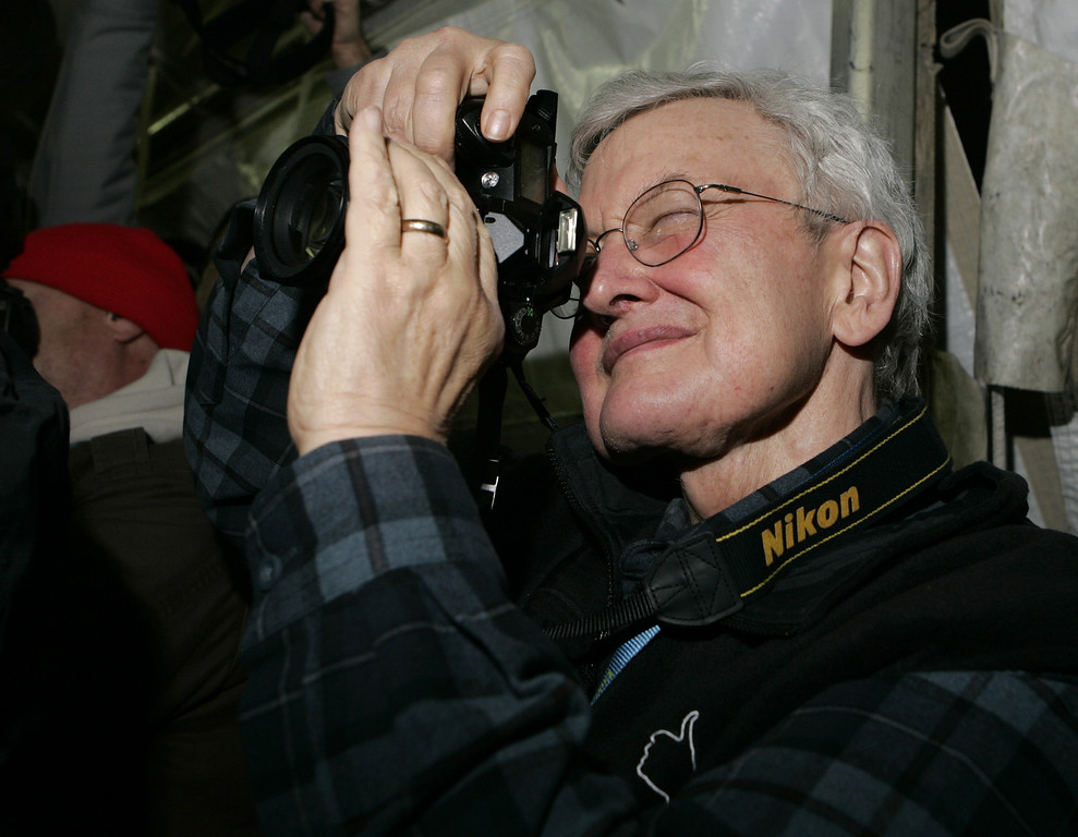 "Description of . Movie critic Roger Ebert  photographs ""The Darwin Awards\"" director Finn Taylor from the media line before the the screening of the film during the Sundance Film Festival in Park City, Utah, Wednesday, Jan. 25, 2006. (AP Photo/Carolyn Kaster)"
