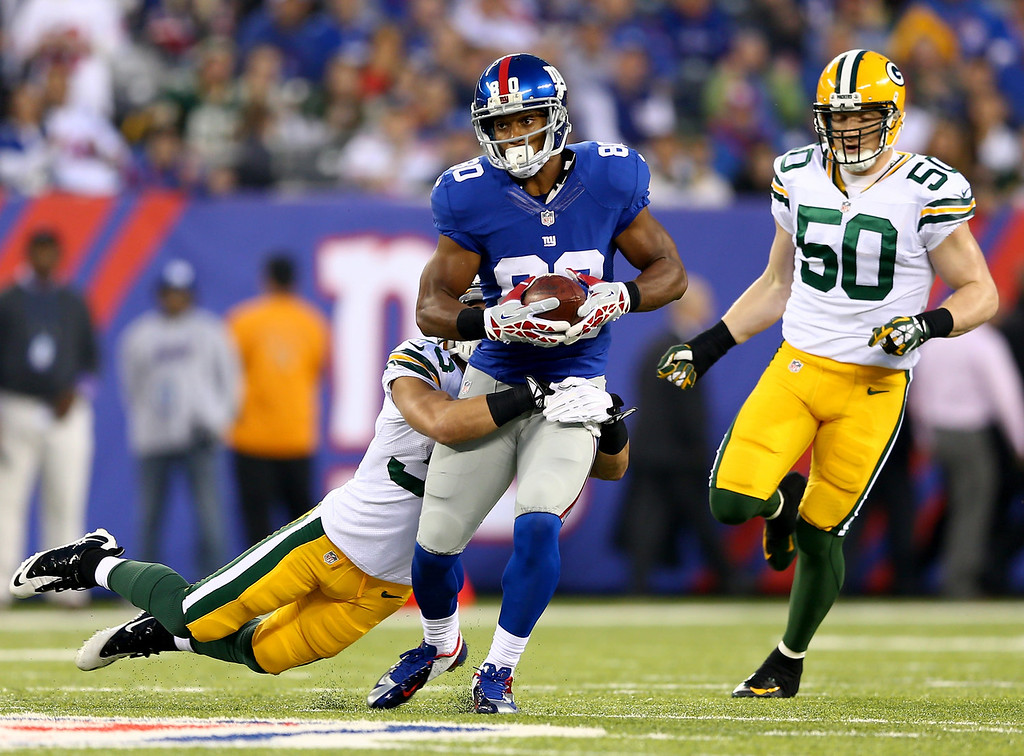 Description of . Victor Cruz #80 of the New York Giants is tackled by  Micah Hyde #33 of the Green Bay Packers at MetLife Stadium on November 17, 2013 in East Rutherford, New Jersey.  (Photo by Elsa/Getty Images)