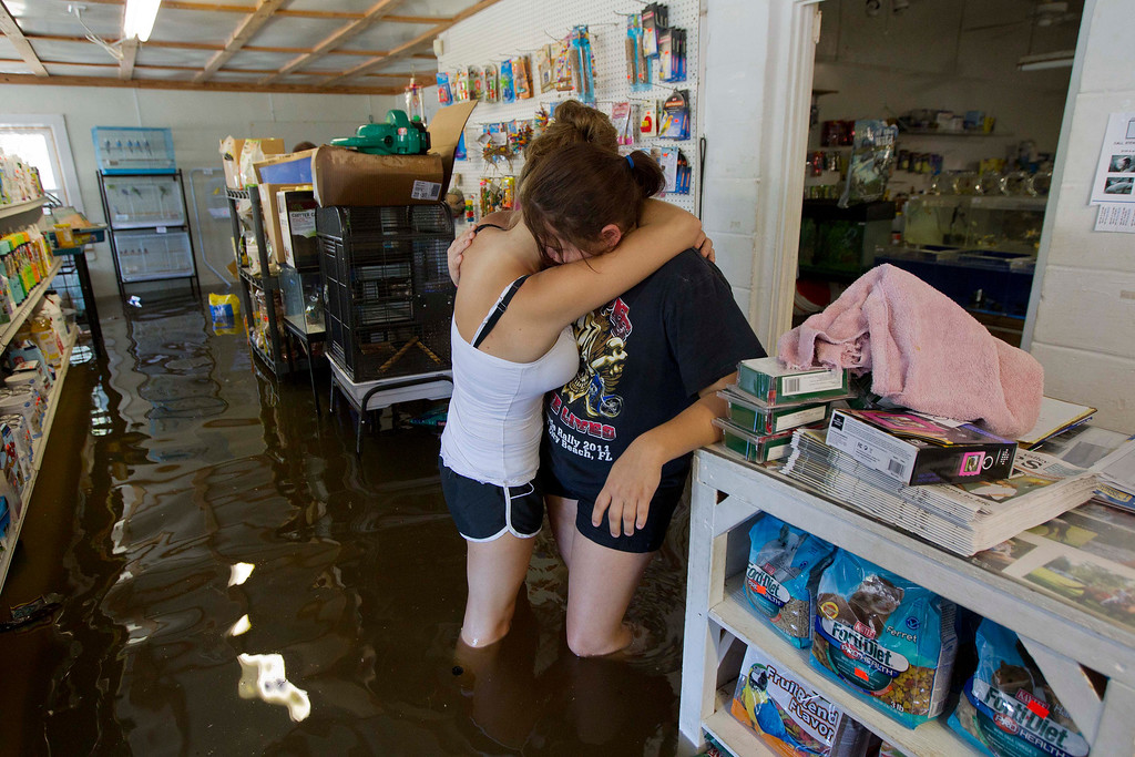 Description of . In this June 27, 2012 file photo, Tarra Piet, right, is embraced by her cousin Kursty Setty as they stand in Piet's fathers flooded pet store Live Oak Fla. Dozens of homes and businesses were flooded by torrential rains from Tropical Storm Debby. (AP Photo/Dave Martin, File)