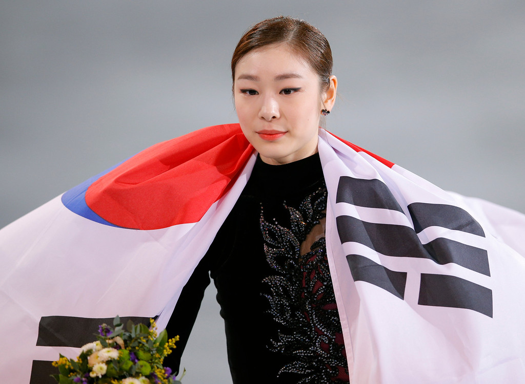Description of . Yuna Kim of South Korea celebrates her second place with the national flag following the flower ceremony for the women's free skate figure skating finals at the Iceberg Skating Palace during the 2014 Winter Olympics, Thursday, Feb. 20, 2014, in Sochi, Russia. (AP Photo/Vadim Ghirda)