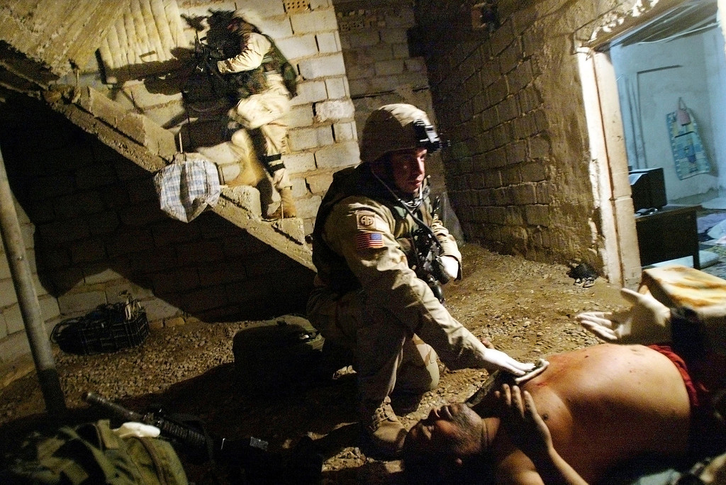 "Description of . U.S. Army combat medic Sgt. Luis Pacheco of the 1st Brigade, 505th Parachute Infantry Regiment of the 82nd Airborne Division, from Chicago, Illinois, treats an Iraqi ""insurgent\"" for a gunshot wound to the chest as another soldier searches the home during early morning raids January 6, 2004 in Fallujah, Iraq. The Army said the man was fired upon by U.S. soldiers after brandishing a rifle. The raids netted four suspects including an Iraqi man suspected of constructing IED\'s for insurgents. (Photo by Mario Tama/Getty Images)"
