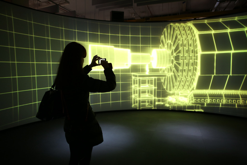 Description of . A visitor to the Science Museum takes a phone photograph of a video projection showing the workings of the Large Hadron Collider (LHC)  at the 'Collider' exhibition on November 12, 2013 in London, England.  (Photo by Peter Macdiarmid/Getty Images)