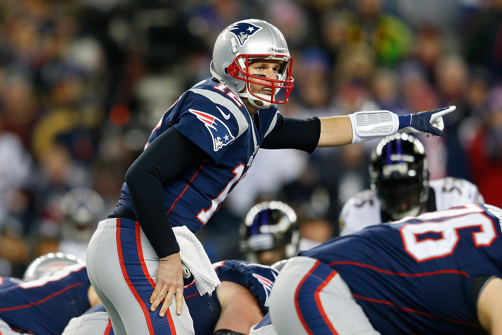 Description of . Tom Brady #12 of the New England Patriots makes an adjustment at the line against the Baltimore Ravens during the 2013 AFC Championship game at Gillette Stadium on January 20, 2013 in Foxboro, Massachusetts.  (Photo by Jim Rogash/Getty Images)