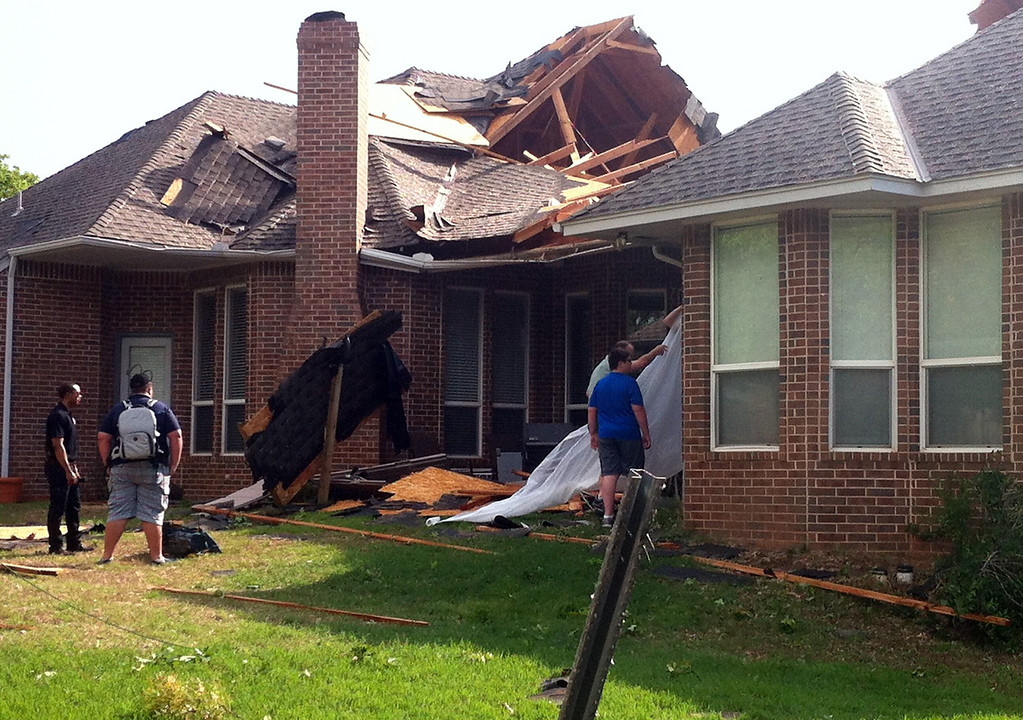Description of . Residents of Edmond, Okla., survey storm damage from a tornado that hit their neighborhood Sunday, May 19, 2013. Forecasters had warned that the middle of the country would see severe weather throughout the weekend. (AP Photo/Sean Murphy)