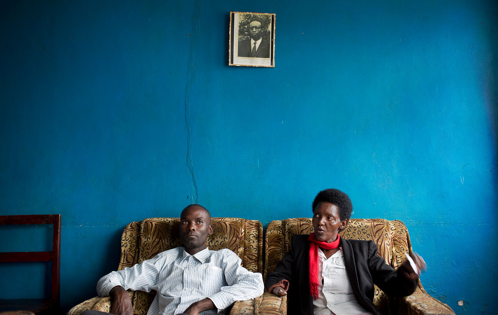 Description of . In this photo taken Wednesday, March 26, 2014, Emmanuel Ndayisaba, left, and Alice Mukarurinda, recount their experiences of the Rwandan genocide as they sit under a photograph of Alice's father, who was elsewhere at the time and also managed to survive, at Alice's house in Nyamata, Rwanda. She lost her baby daughter and her right hand to a manic killing spree. He wielded the machete that took both. Yet today, despite coming from opposite sides of an unspeakable shared past, Alice Mukarurinda and Emmanuel Ndayisaba are friends. She is the treasurer and he the vice president of a group that builds simple brick houses for genocide survivors. They live near each other and shop at the same market. Their story of ethnic violence, extreme guilt and, to some degree, reconciliation is the story of Rwanda today, 20 years after its Hutu majority killed more than 1 million Tutsis and moderate Hutus. The Rwandan government is still accused by human rights groups of holding an iron grip on power, stifling dissent and killing political opponents. But even critics give President Paul Kagame credit for leading the country toward a peace that seemed all but impossible two decades ago. (AP Photo/Ben Curtis)