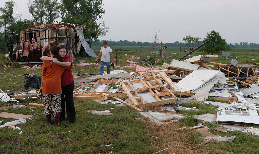 Description of . Leah Hill (L), of Shawnee, Oklahoma, is hugged by friend Sidney Sizemore, as they look through Hill's scattered belongings from her home which was destroyed by a tornado, west of Shawnee, Oklahoma May 19, 2013  A tornado half a mile wide struck near Oklahoma City on Sunday, part of a massive storm front that hammered the central United States. News reports said at least one person had died. REUTERS/Bill Waugh