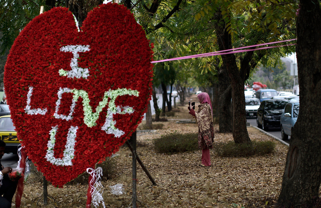 . A Pakistani woman uses her mobile phone to take a picture of flowers displayed for sale outside a shop on Valentine\'s Day, in Islamabad, Pakistan, Thursday, Feb. 14, 2013.  (AP Photo/Muhammed Muheisen)