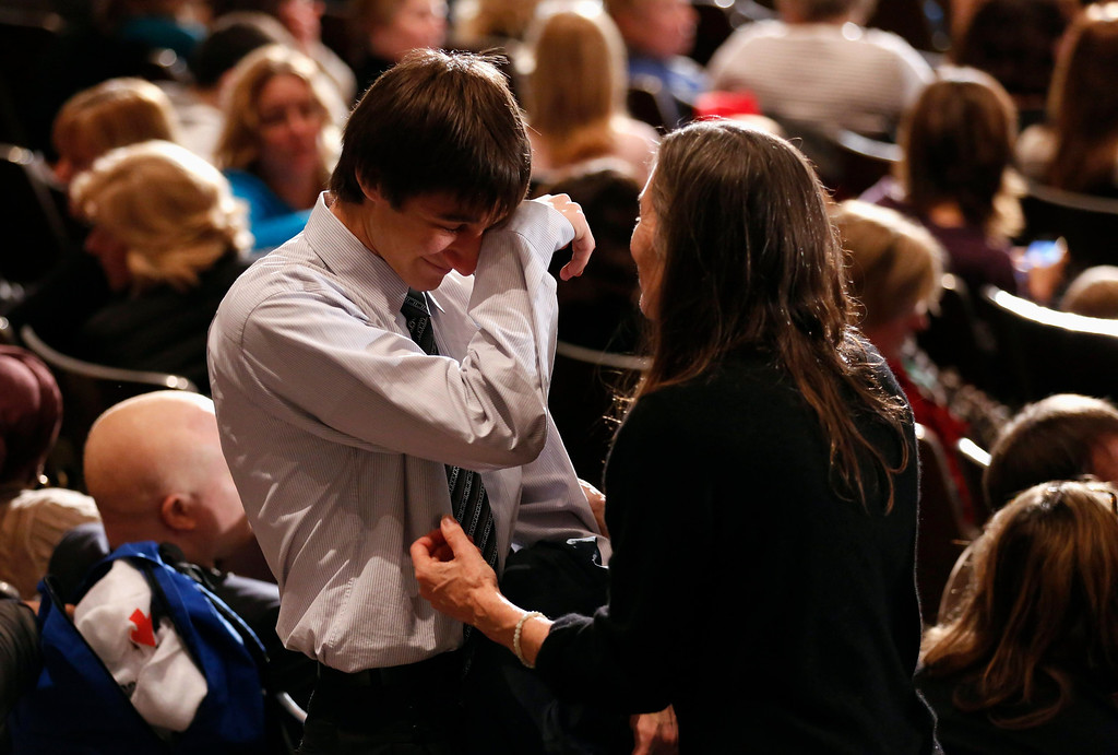 Description of . A young man is comforted during a vigil held at Newtown High School for families of victims of the Sandy Hook Elementary School shooting in Newtown, Connecticut December 16, 2012. U.S. President Barack Obama is visiting Newtown High School to meet with the families of the victims and to thank first responders to the school shooting here, which was one of the deadliest such incidents in the nation's history. REUTERS/Kevin Lamarque