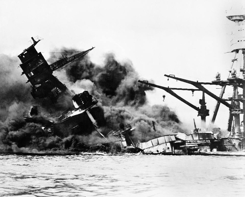 Description of . The battleship USS Arizona belches smoke as it topples over into the sea during Japanese surprise attack on Pearl Harbor, Hawaii, December 7, 1941. The ship sank with more than 80 percent of its 1,500-man crew, including Rear Admiral Issac C. Kidd. The attack, which left 2,343 Americans dead and 916 missing, broke the backbone of the U.S. Pacific Fleet and forced America out of a policy of isolationism. President Franklin D. Roosvelt announced that it was