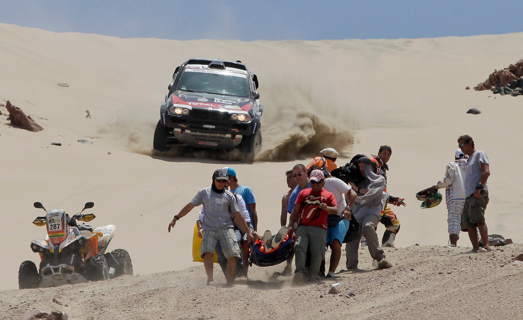Description of . Orlando Terranova of Argentina and co-driver Paulo Fiuza of Portugal drive their BMW, top, as medics evacuate Leonardo Martinez of Bolivia after crashing with his quad in the 3nd stage of the 2013 Dakar Rally from Pisco to Nazca, Peru, Monday, Jan. 7, 2013. The race finishes in Santiago, Chile, on Jan. 20. (AP Photo/Victor R. Caivano)
