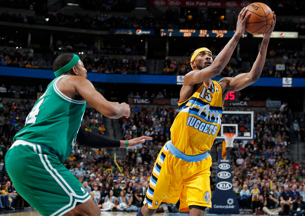 Description of . Denver Nuggets forward Corey Brewer, right, slips past Boston Celtics forward Paul Pierce for a shot  in the fourth quarter of the Nuggets' 97-90 victory in an NBA basketball game in Denver on Tuesday, Feb. 19, 2013. (AP Photo/David Zalubowski)