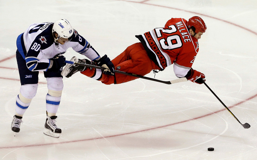. Carolina Hurricanes\' Tim Wallace (29) is upended by Winnipeg Jets\' Nik Antropov (80), of Kazakhstan, during the third period of an NHL hockey game in Raleigh, N.C., Thursday, Feb. 21, 2013. Winnipeg won 4-3. (AP Photo/Gerry Broome)