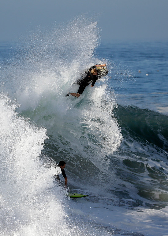 Description of . A bogie boarder and a surfer ride a wave at the wedge, on Wednesday, Aug. 27, 2014 in Newport Beach, Calif. Beach goers experienced much higher than normal surf, brought on by Hurricane Marie spinning off the coast of Mexico. (AP Photo/Chris Carlson)