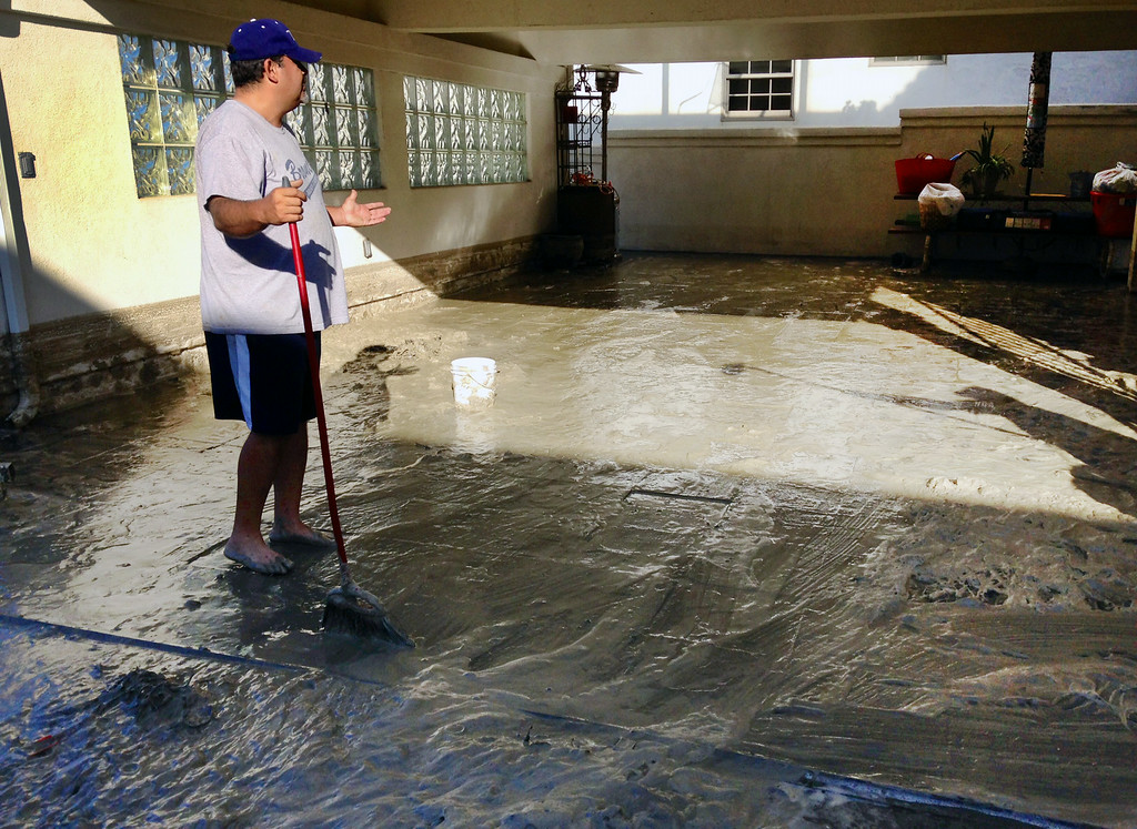 Description of . Hector Brown sweeps out his aunt and uncle's house in Seal Beach, Calif. on Wednesday, Aug. 27, 2014. The entire house and garage was flooded by a foot of water and muddy sand late Tuesday night after low-lying streets in the Southern California coastal community was inundated by a surge of rising seawater brought on by Hurricane Marie spinning off Mexico's Pacific coast. (AP Photo/Gillian Flaccus)