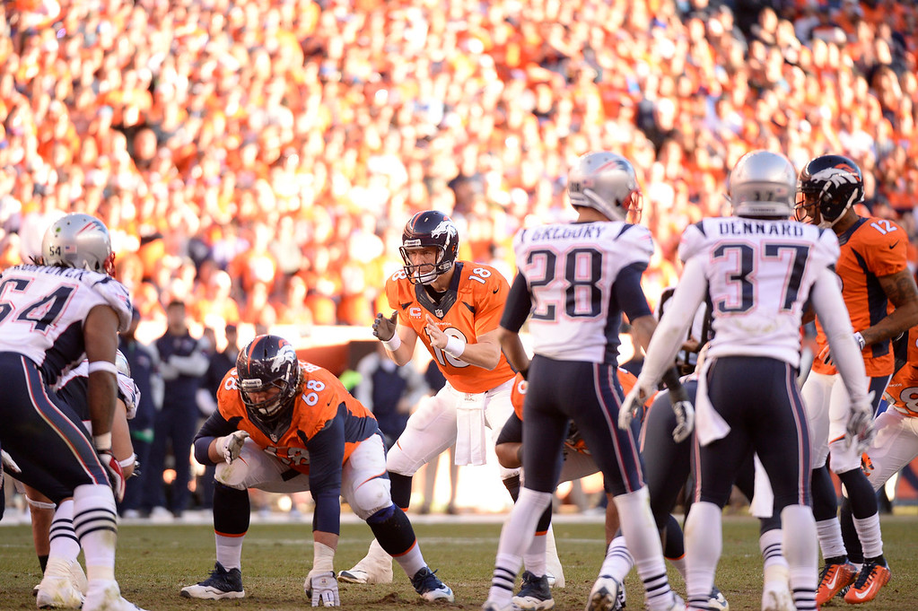 Description of . Denver Broncos quarterback Peyton Manning (18) runs the offense during the fourth quarter. The Denver Broncos vs. The New England Patriots in an AFC Championship game  at Sports Authority Field at Mile High in Denver on January 19, 2014. (Photo by John Leyba/The Denver Post)
