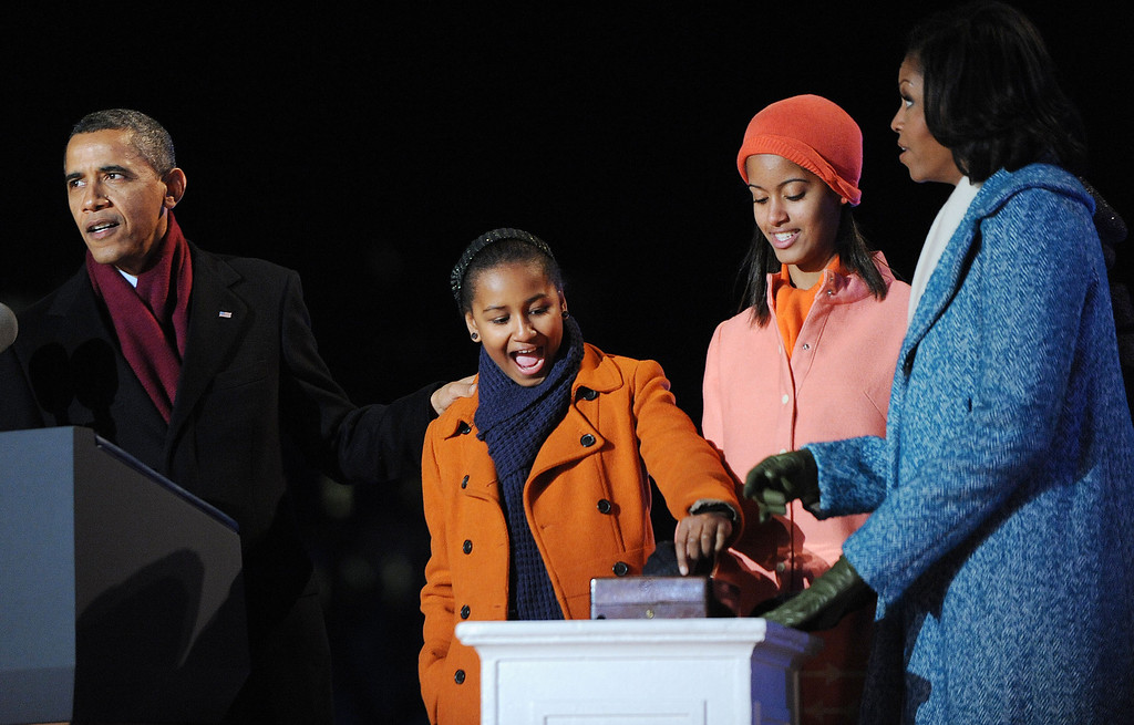 Description of . U.S. President Barack Obama (L) with his wife first lady Michelle Obama (R) and their daughters Malia (2nd R) and Sasha Obama light the 90th National Christmas Tree during the Lighting Ceremony on the Ellipse behind the White House on December 6, 2012 in Washington, DC. This year is the 90th annual National Christmas Tree Lighting Ceremony. (Photo by Olivier Douliery-Pool/Getty Images)