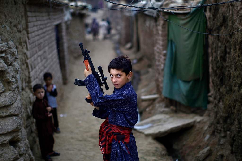 . An Afghan refugee boy poses with a plastic rifle as he and other children celebrate the first day of the Eid al-Fitr festival, which marks the end of the Muslim fasting month of Ramadan, in a slum on the outskirts of Islamabad, Pakistan, Monday, Aug. 20, 2012. Muslims around the world are celebrating Eid al-Fitr, marking the end of Ramadan, the Muslim calendar\'s ninth and holiest month during which followers are required to abstain from food and drink from dawn to dusk. (AP Photo/Muhammed Muheisen)