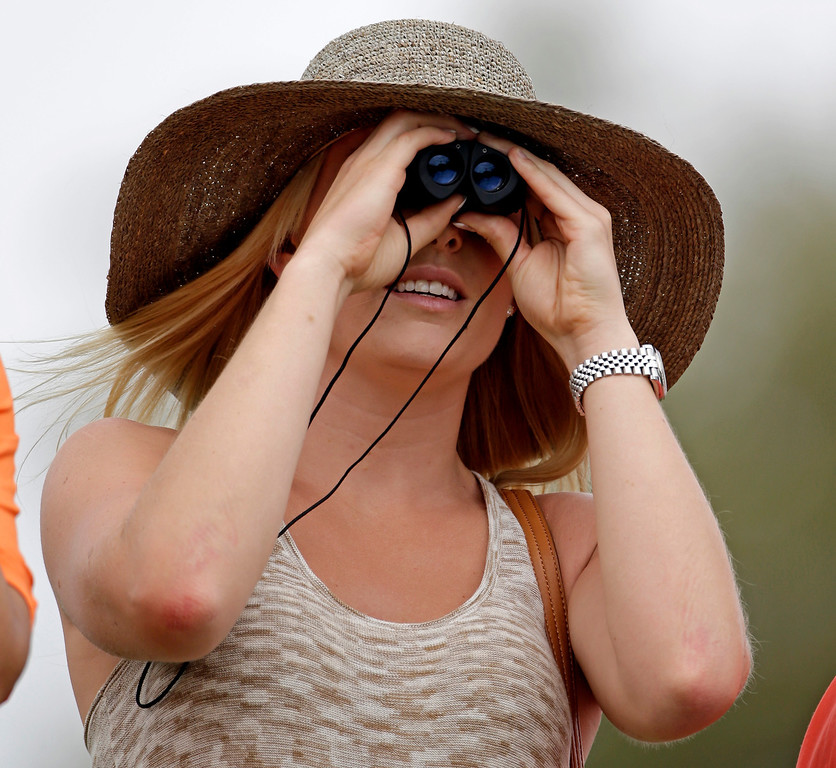 . Skier Lindsey Vonn tries a pair binoculars to watchTiger Woods during the first round of the Masters golf tournament Thursday, April 11, 2013, in Augusta, Ga. (AP Photo/Darron Cummings)