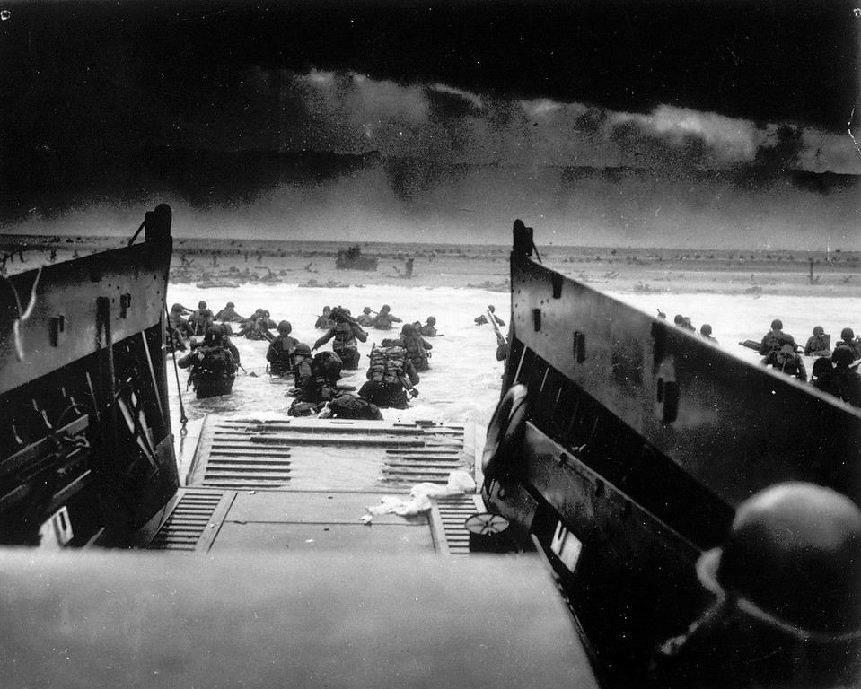 Description of . While under attack of heavy machine gun fire from the German coastal defense forces, these American soldiers wade ashore off the ramp of a U.S. Coast Guard landing craft, June 6, 1944, during the Allied landing operations at the Normandy. (AP Photo)