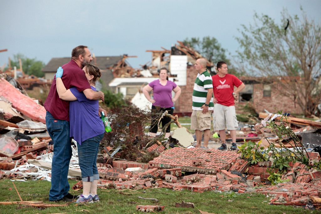 . Glenn Rusk hugs his neighbor Sherie Loman outside her home north of Briarwood Elementary School after a tornado moved through the area, in Moore, Okla., Monday, May 20, 2013. (AP Photo/The Oklahoman, David McDaniel)