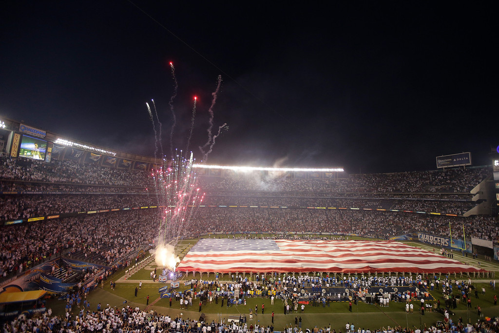 Description of . Members of the National Guard hold up a giant American flag during the National Anthem before in an NFL football game between the San Diego Chargers and the Houston Texans Monday, Sept. 9, 2013, in San Diego. (AP Photo/Chris Carlson)