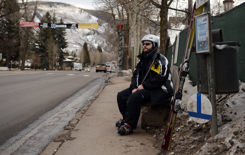 Description of . ASPEN, CO. - JANUARY 24:  The 2013. Winter X Games officially kicked off in Aspen. Dan Baptist, who is visiting Aspen during the X Games waits for a bus, January 24, 2013,in downtown Aspen. (Photo By RJ Sangosti / The Denver Post)