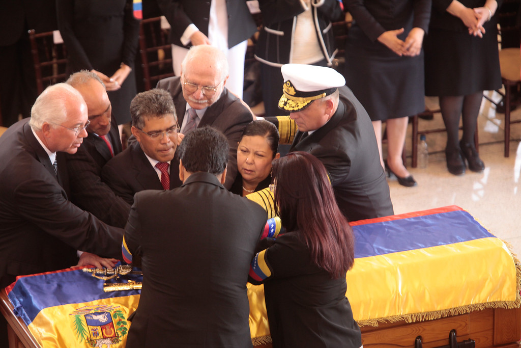 Description of . In this photo released by Miraflores Press Office, Venezuelan government officials join hands over the flag-draped casket of Venezuela's late President Hugo Chavez during a funeral ceremony at the military academy in Caracas, Venezuela, Friday, March 8, 2013. (AP Photo/Miraflores Press Office)