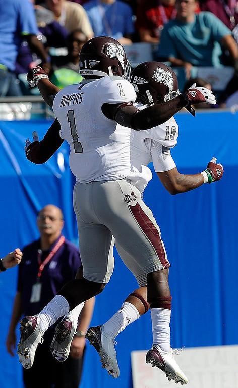 Description of . Mississippi State wide receivers Arceto Clark (19) and Chad Bumphis (1) celebrate Clark's touchdown catch against Northwestern during the first half of the Gator Bowl NCAA college football game, Tuesday, Jan. 1, 2013, in Jacksonville, Fla. (AP Photo/Stephen Morton)