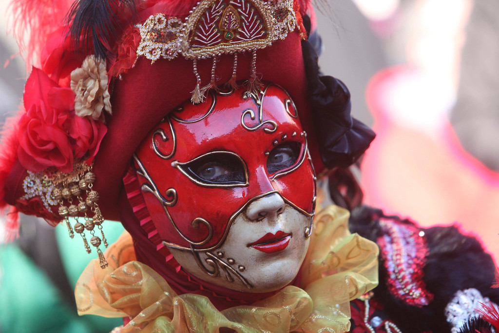 Description of . A woman dressed in traditional costume looks on during the Venetian Carnival in Saint Mark's square in Venice February 3, 2013.  REUTERS/Manuel Silvestri