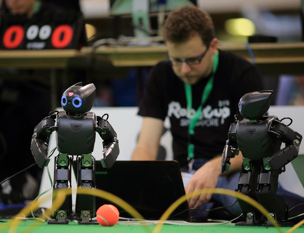 Description of . A technicians configures robots for a match during the