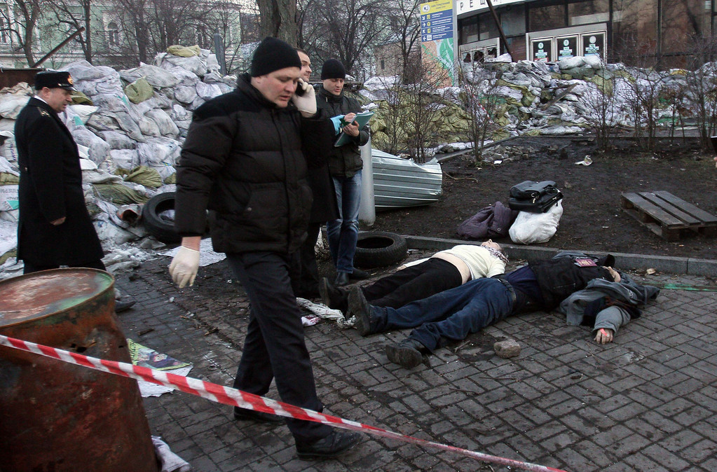 Description of . Police experts examine bodies of the dead anti-government protesters after their clashes with the police in Kiev on February 18, 2014. AFP PHOTO/ ANATOLII  BOIKO/AFP/Getty Images