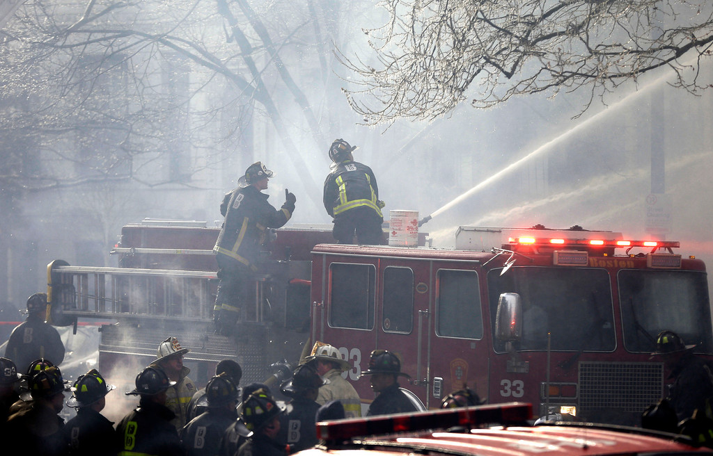 Description of . Fighters battle a multi-alarm fire at a four-story brownstone in the Back Bay neighborhood near the Charles River, Wednesday, March 26, 2014, in Boston.  (AP Photo/Steven Senne)