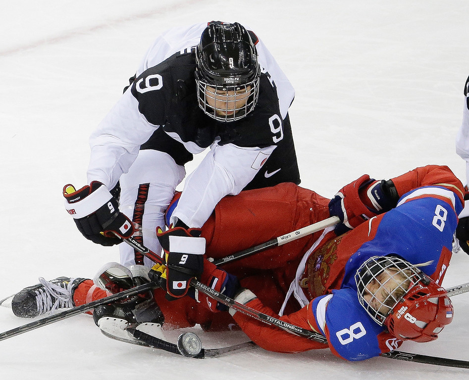 Description of . Aina Takeuchi of Japan collides with Iya Govrilova of Russia during the third period of the 2014 Winter Olympics women\'s ice hockey game at Shayba Arena, Tuesday, Feb. 11, 2014, in Sochi, Russia. Russia defeated Japan 2-1. (AP Photo/Mark Humphrey)