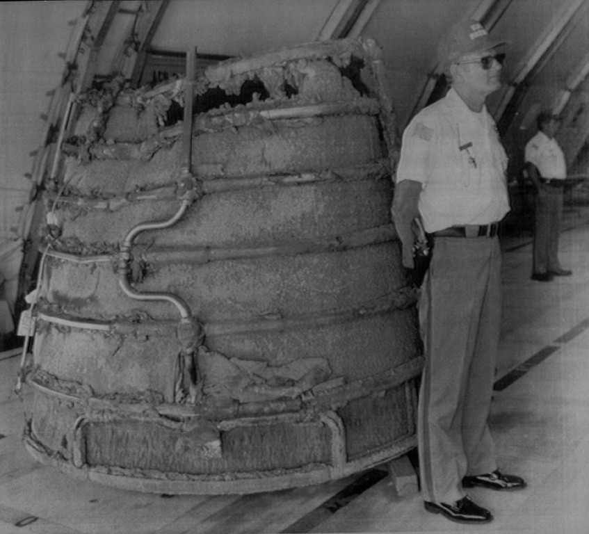 Description of . A security guard at Kennedy Space Center stands guard near the space shuttle Challenger\'s main engine bell Wednesday, April 1, 1986. The media was shown the wreckage of the Challenger for the first time today, following the January 28 explosion which took the lives of all seven astronauts.  Denver Post Library Archive