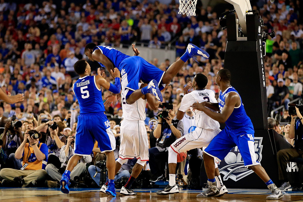 Description of . ARLINGTON, TX - APRIL 07: Alex Poythress #22 of the Kentucky Wildcats falls over DeAndre Daniels #2 of the Connecticut Huskies during the NCAA Men\'s Final Four Championship at AT&T Stadium on April 7, 2014 in Arlington, Texas.  (Photo by Jamie Squire/Getty Images)