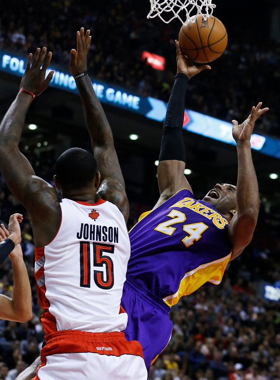 Description of . Los Angeles Lakers' Kobe Bryant (R) goes the the basket against Toronto Raptors' Amir Johnson during the second half of their NBA basketball game in Toronto, January 20, 2013.     REUTERS/Mark Blinch