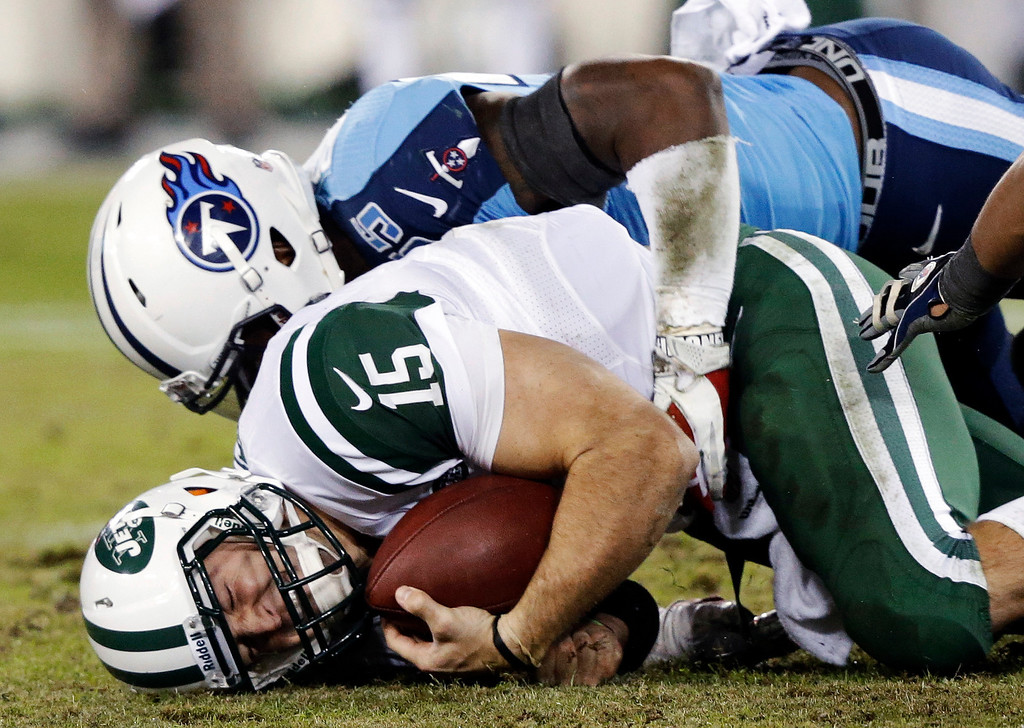 Description of . New York Jets quarterback Tim Tebow (15) is sacked for a 2-yard loss by Tennessee Titans linebacker Zach Brown (55) in the second quarter of an NFL football game, Monday, Dec. 17, 2012, in Nashville, Tenn. (AP Photo/Wade Payne)