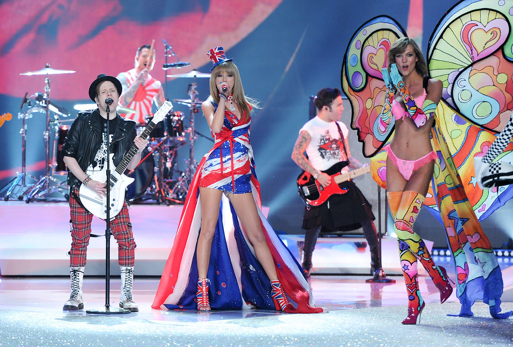 Description of . Singer Taylor Swift, center, performs with Fall Out Boy during the 2013 Victoria's Secret Fashion Show at the 69th Regiment Armory on Wednesday, Nov. 13, 2013, in New York. (Photo by Evan Agostini/Invision/AP)