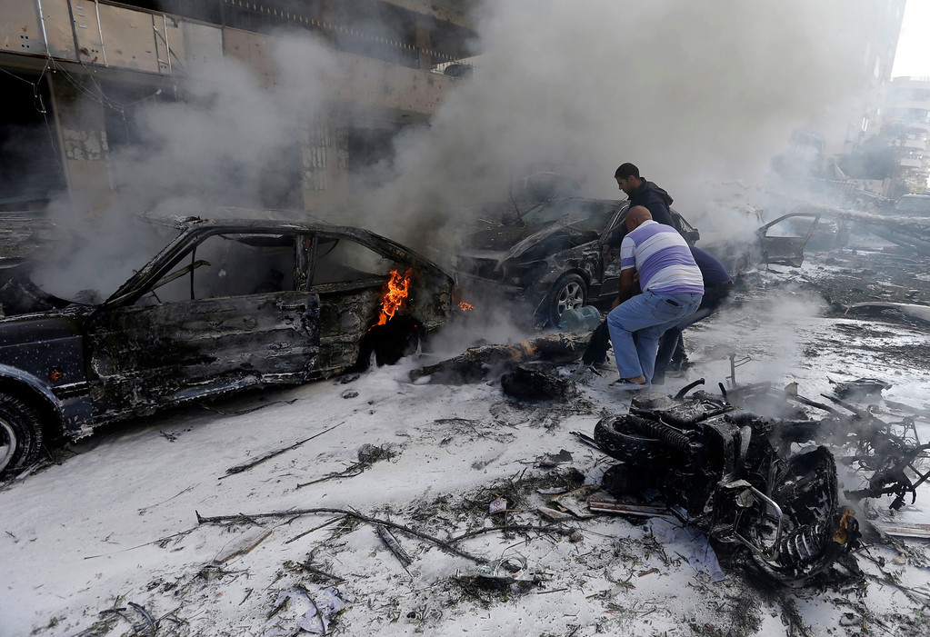 Description of . Two Lebanese men remove a dead body from a burned car, at the scene where two explosions have struck near the Iranian Embassy killing many, in Beirut, Lebanon, Tuesday Nov. 19, 2013.  (AP Photo/Hussein Malla)
