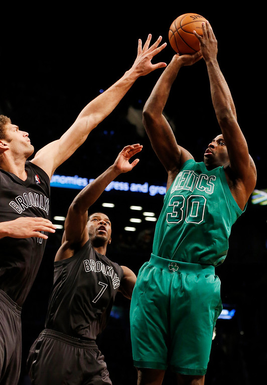 Description of . Boston Celtics forward Brandon Bass (30) shoots over Brooklyn Nets center Brook Lopez (11) and guard Joe Johnson (7) in the second half of their NBA basketball game at Barclays Center, Tuesday, Dec. 25, 2012, in New York. Boston won 93-76. (AP Photo/John Minchillo)