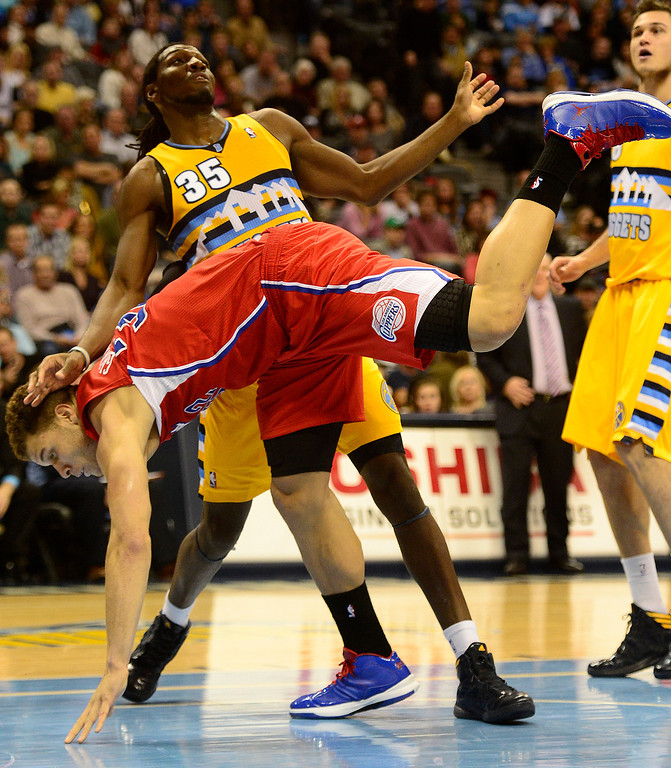 Description of . Los Angeles Clippers power forward Blake Griffin (32) falls to the ground as Denver Nuggets small forward Kenneth Faried (35) avoids contact during the second half of the Nugget's 92-78 win at the Pepsi Center on Tuesday, January 1, 2013. AAron Ontiveroz, The Denver Post