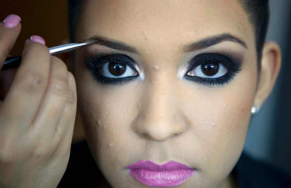 Description of . In this Jan. 26, 2013 photo, beauty contestant Donaji Lopez holds still as her make-up is applied backstage before competing in the