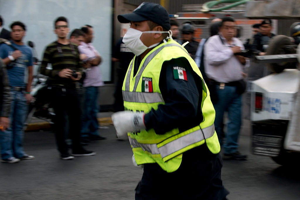 Description of . A paramedic rushes into the skyscraper that houses the headquarters of state-owned Mexican oil giant Pemex, following a blast inside the building in Mexico City on January 31, 2013. An explosion rocked the skyscraper, killing at least 14 people. AFP PHOTO/Yuri CORTEZ