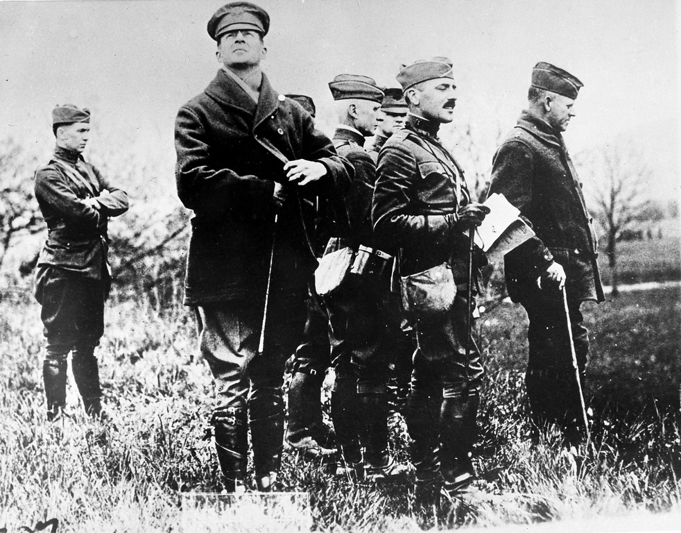 Description of . Col. Douglas MacArthur, second from left, looking up, watches practice maneuvers with his staff at Baccarat, France, during the Great War, May 9, 1918. Major General Charles T. Menoher, right, with cane, was also in the group. (AP Photo)