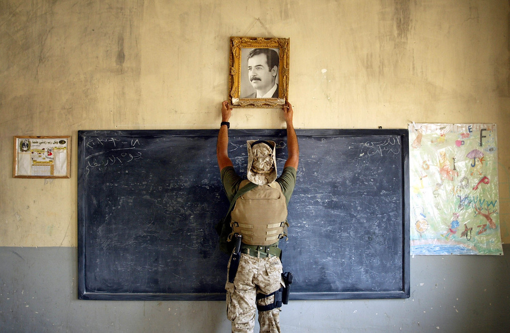 Description of . A U.S. Marine pulls down a picture of Saddam Hussein at a school April 16, 2003 in Al-Kut, Iraq. A combination team of Marines, Army and Special Forces went to schools and other facilities in Al-Kut looking for weapons caches and unexploded bombs in preparation for removing and neutralizing them. (Photo by Chris Hondros/Getty Images)