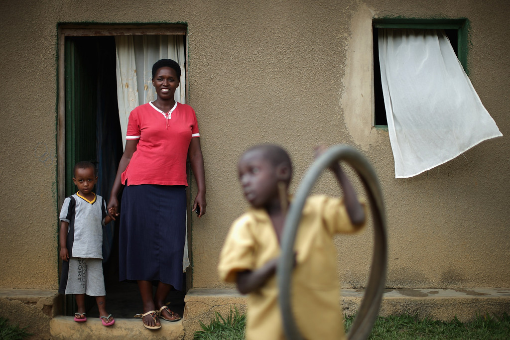 """. Jeanette Mukabyagaju, 35, stands in the doorway of her home with her daughter Natasha, 3, in a genocide \""""reconciliation village\"""" April 6, 2014 in Mybo, Rwanda. 7 members of Jeanette\'s immediate family were killed in the 1994 genocide and she was apprehensive about moving into this planned village 8 years ago. But when her new neighbors, people who had been in prison for genocide, wept while asking for forgiveness, she was comfortable about living in Mbyo. Organized by the Prison Fellowship Rwanda in 2004, this village of 285 is where those who served time in prison for genocide now live side-by-side with people who survived the killer\'s 1994 rampage. One of five communities like this in Rwanda, Mbyo residents share agriculture and handicraft cooperatives and say that working together has helped with reconciliation, easing their apprehension and fostering new friendships. Rwanda is preparing to commemorate the 20th anniversary of the country\'s 1994 genocide, when more than 800,000 ethnic Tutsi and moderate Hutus were slaughtered over a 100 day period.  (Photo by Chip Somodevilla/Getty Images)"""