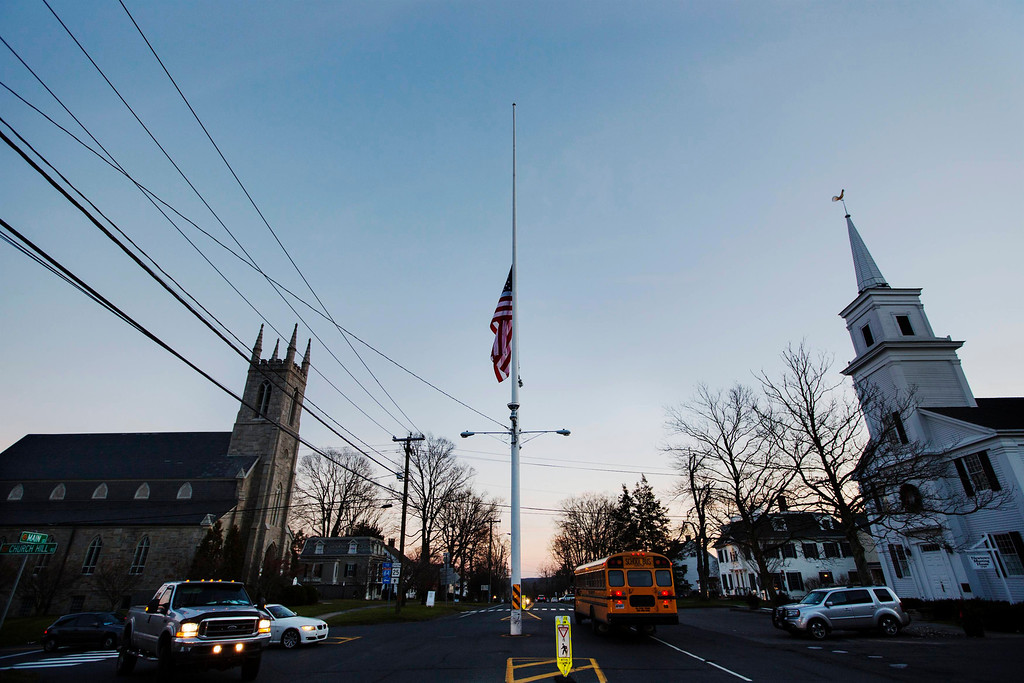 Description of . A U.S. flag flies at half staff as a school bus drives past in the town of Newtown, Connecticut after a shooting nearby at Sandy Hook Elementary School, December 14, 2012. A heavily armed gunman opened fire inside a Connecticut elementary school on Friday, killing 26 people, including 20 children, in the latest in a series of shooting rampages across the United States this year, U.S. media reported. REUTERS/Lucas Jackson