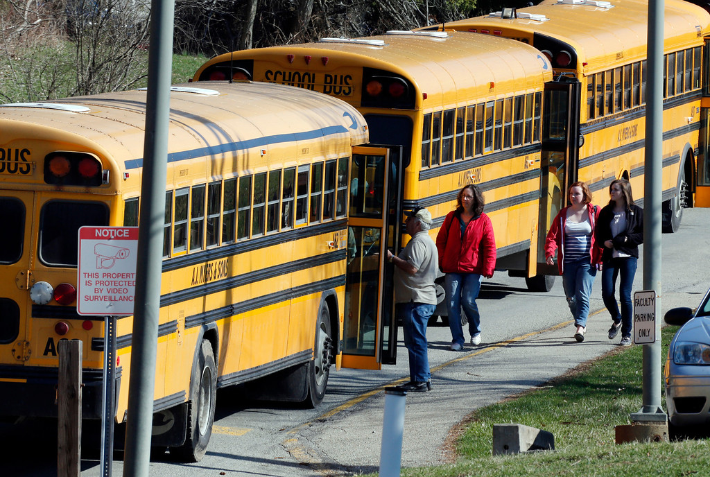 Description of . Students walk past a row of buses as they leave the campus of the Franklin Regional School District after more then a dozen students were stabbed by a knife wielding suspect at nearby Franklin Regional High School on Wednesday, April 9, 2014, in Murrysville, Pa., near Pittsburgh. The suspect, a male student, was taken into custody and is being questioned. (AP Photo/Gene J. Puskar)