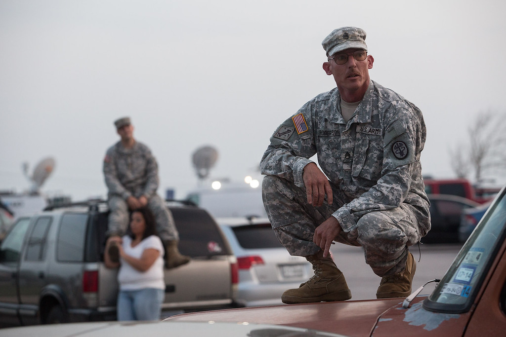 Description of . Staff Sgt. John Robertson, right, waits in a parking lot outside of the Fort Hood military base for updates about the shooting that occurred inside on Wednesday, April 2, 2014, in Fort Hood, Texas. (AP Photo/Tamir Kalifa)