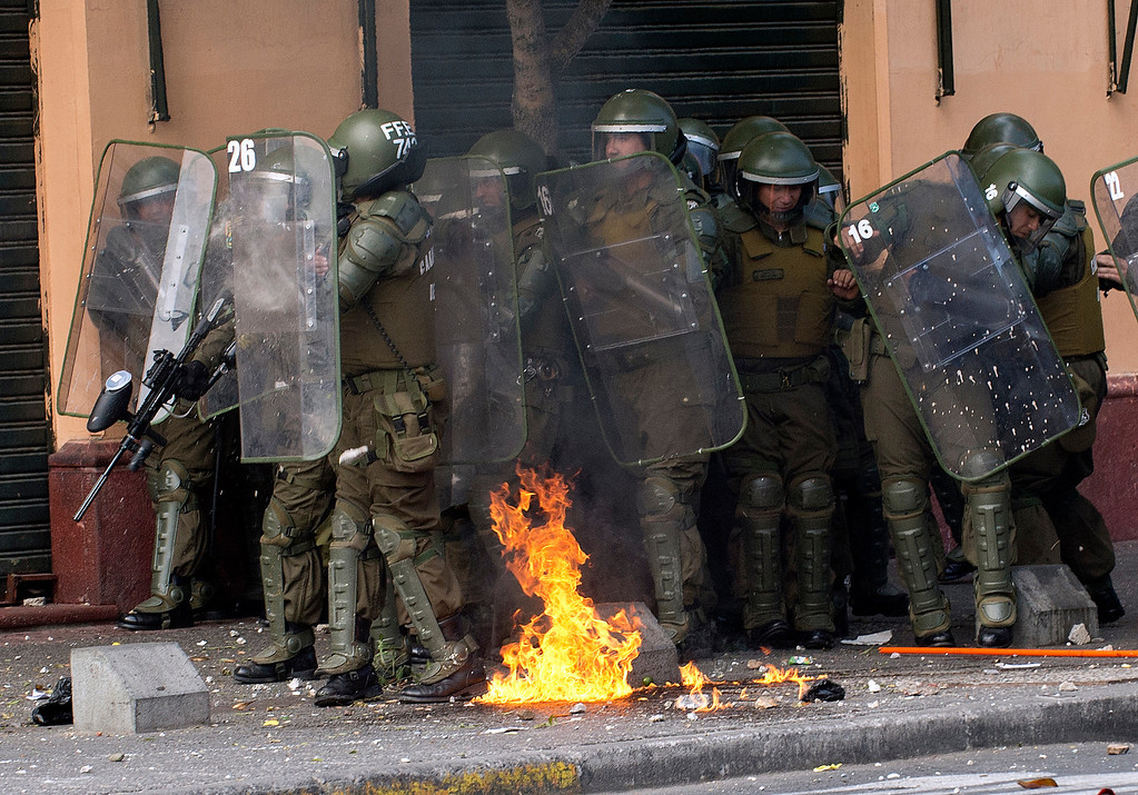 Description of . Riot policemen protect themselves during a student protest who demand Chilean President Sebastian Pinera\'s government to improve the public education quality, in Santiago, on April 11,2013. MARTIN BERNETTI/AFP/Getty Images